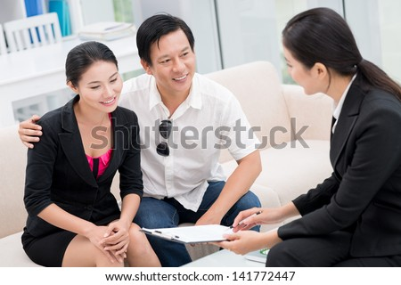 Back view of a realtor working with her clients at the office - stock photo