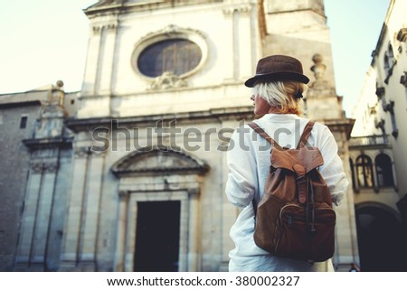 Back view of a stylish female tourist admires of a beautiful architectural building during walking in foreign city, young woman traveler with a rucksack on her back examines historical places - stock photo