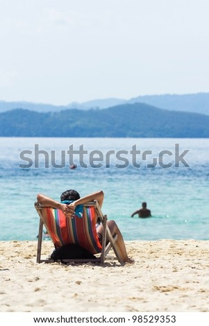 Back View of A Woman on a Beach Chair by the Sea - stock photo