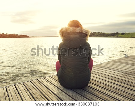 Back view of a woman sitting close to a lake - stock photo