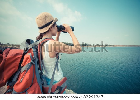 Back view of a young backpacker with binoculars  - stock photo