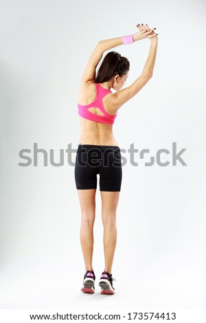 Back view of a young beautiful sport woman stretching on gray background - stock photo