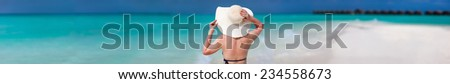 Back view of a young beautiful woman in a white straw hat at tropical beach. Wide panorama with a lot of copy space, perfect for banners - stock photo