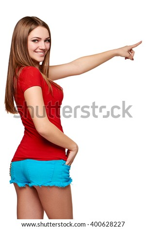 Back view of a young bright female pointing at blank copy space, over white background - stock photo