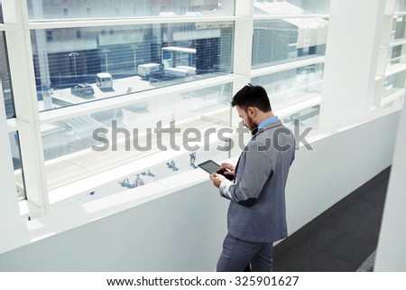 Back view of a young businessman dressed in elegant suit holding touch pad while standing in the hallway of his company, successful male ceo in elegant clothes using digital tablet during work break - stock photo