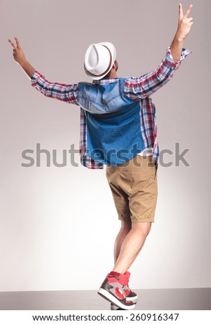Back view of a young casual man celebrating a victory by holding his hands up.. - stock photo