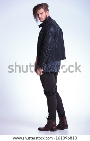 back view of a young fashion man in leather jacket looking at the camera - stock photo