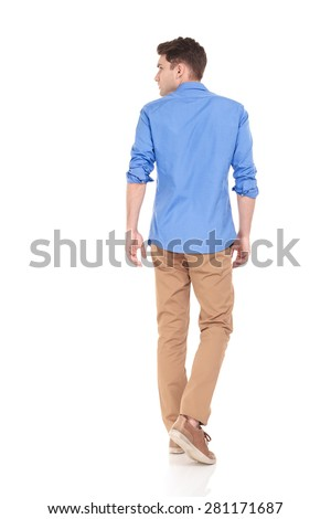 Back view of a young fashion man walking on isolated background looking to his side. - stock photo