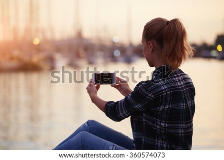 Back view of a young female making photo with her mobile phone digital camera while relaxing in the fresh air in summer evening, woman tourist photographing beautiful sea landscape on cell telephone - stock photo