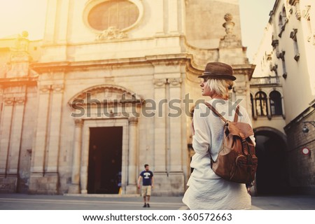 Back view of a young female wanderer out sightseeing in a foreign city during weekend overseas, trendy woman traveler with a rucksack on her back walking on unfamiliar street during summer adventure  - stock photo