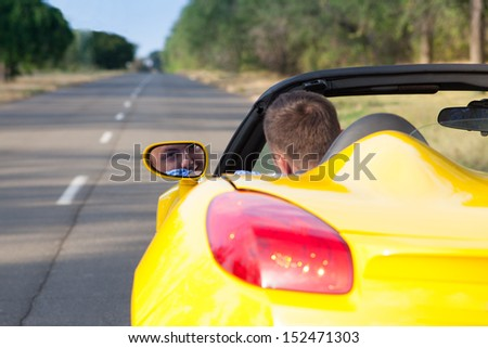 Back view of a young man driving his convertible yellow car. Open roof - stock photo