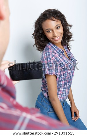 Back view of a young man making a photo of his charming mulatto girlfriend posing for him and smiling, isolated on grey background, selective focus - stock photo