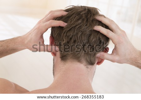 back view of  a young man suffering from itchy scalp - stock photo