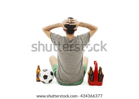 Back view of a young man with soccer ball and pack of beer watching football game, look disappointed. Rear view. Isolated on white background  - stock photo