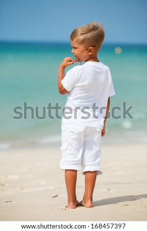 Back view of adorable cute boy on beach vacation - stock photo