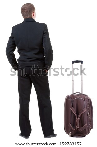 back view of adult man in black suit  traveling with suitcas .   Businessman looks ahead.  Isolated over white background. Rear view people collection. backside view of person.  - stock photo