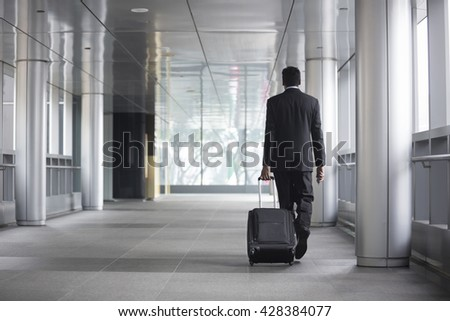 Back view of an Indian businessman walking away from camera in the city. - stock photo