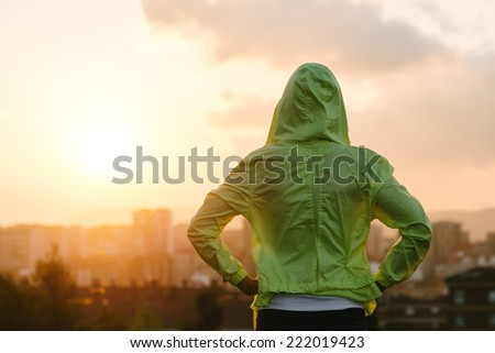 Back view of athlete looking sunset over city skyline after exercising. Motivation, sport and fitness lifestyle concept. - stock photo
