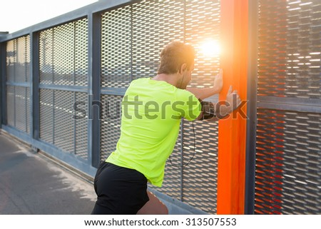 Back view of athletic man stretching his legs while leaning on iron fence in order to start the daily morning jog near stadium, man makes exercises for the legs before began his run at sunrise - stock photo