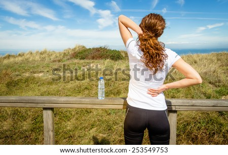 Back view of athletic young woman in sportswear touching her neck and lower back muscles by painful injury, over a nature background. Sport injuries concept. - stock photo