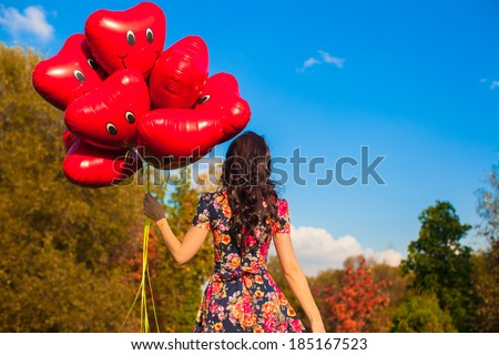 Back view of attractive young woman with red smiling balloons in hand outdoor - stock photo
