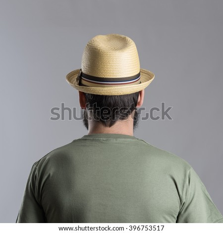 Back view of bearded man with straw hat looking away.  Headshot portrait over gray studio background.  - stock photo