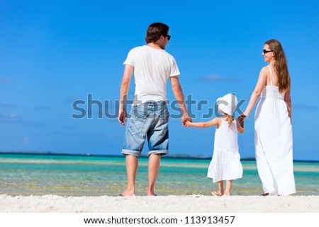 Back view of beautiful family on tropical beach - stock photo
