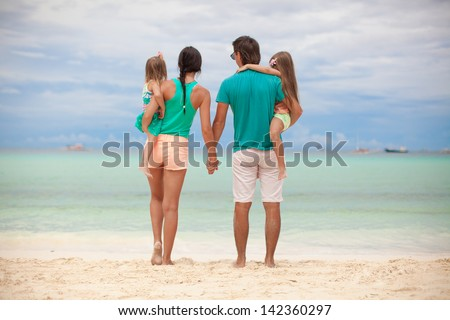 Back view of beautiful family with two daughters at exotic beach on sunny day - stock photo