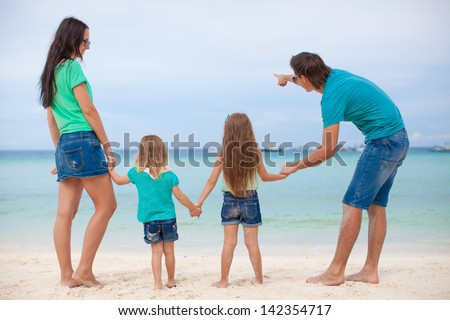 Back view of beautiful family with two kids at exotic beach - stock photo