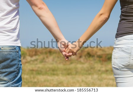 Back view of beautiful love couple holding hands outdoors over a summer field background - stock photo