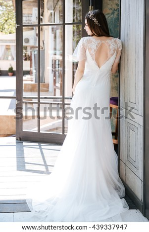 Back view of beautiful young bride in long white dress standing and posing outdoors - stock photo
