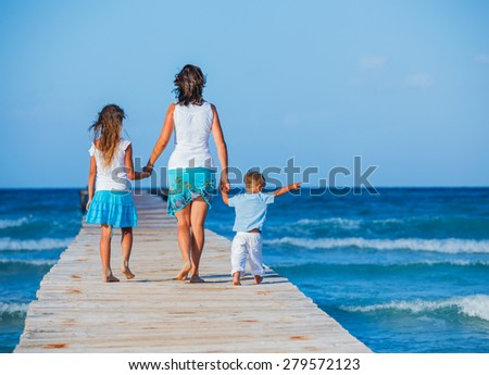 Back view of beautiful young family walking along wooden jetty - stock photo