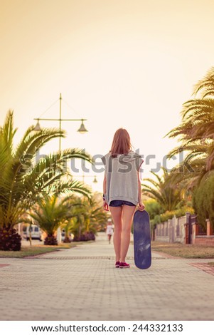 Back view of beautiful young girl with short shorts and skateboard outdoors on a hot summer day. Warm tones edition. - stock photo