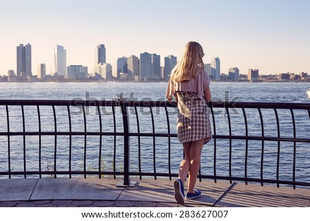 Back view of blonde young woman leaning on berth railing in port on sunny summer day - stock photo