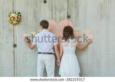 Back view of  bride and groom infront of the wall with pink heart.  - stock photo