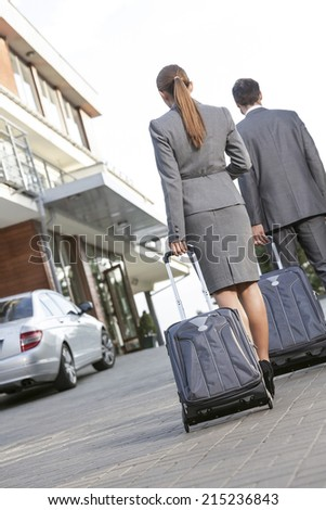 Back view of business couple walking with luggage on driveway - stock photo