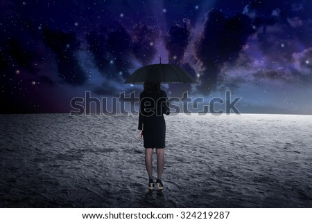 Back view of business man holding umbrella from outer space - stock photo