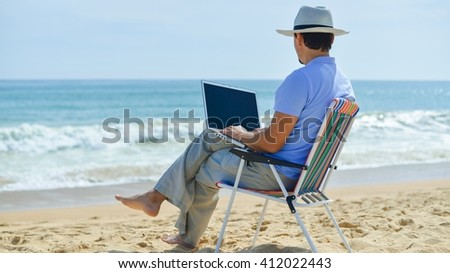 Back view of business man using computer on tropical beach outdoors background. Mockup top view  - stock photo