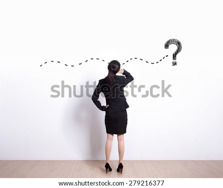 Back view of business woman look and think about complicated questions. Drawn question marks on the white wall. - stock photo