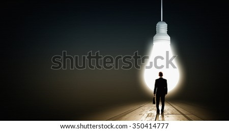 Back view of businessman looking at big glowing light bulb - stock photo