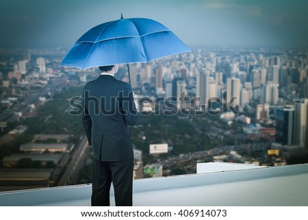 Back view of businessman with umbrella on the rooftop and looking at city - stock photo