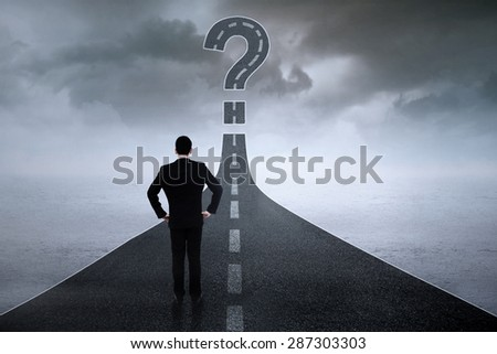 Back view of businessperson standing on the road while looking at question sign - stock photo