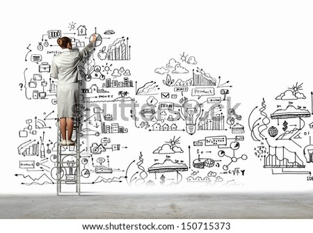 Back view of businesswoman drawing sketch on wall - stock photo