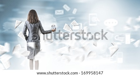 Back view of businesswoman holding alarm clock against city background - stock photo