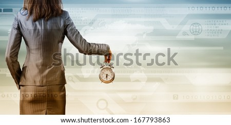 Back view of businesswoman holding alarm clock against media background - stock photo