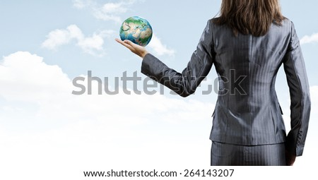 Back view of businesswoman holding earth planet in hand. Elements of this image are furnished by NASA - stock photo