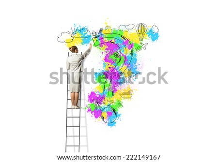 Back view of businesswoman standing on ladder and drawing on wall - stock photo