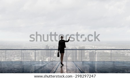 Back view of businesswoman standing on roof looking at city - stock photo