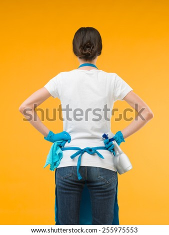 back view of caucasian cleaning woman standing and holding cleaning products against yellow background - stock photo