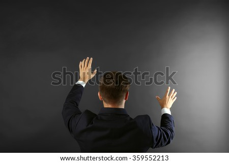 Back view of Caucasian young man in navy blue suit pointing on dark grey background - stock photo